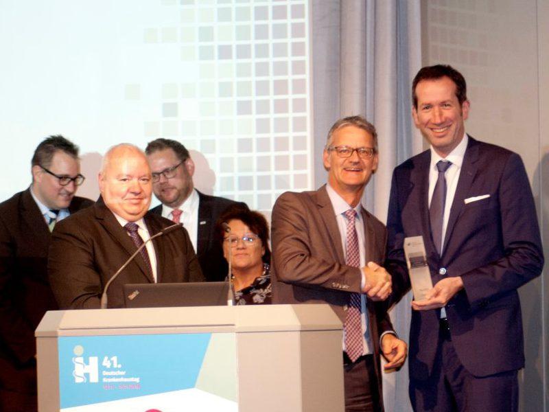 Dr. Gaß, Präsident der Deutschen Krankenhausgesellschaft, überreicht auf dem Deutschen Krankenhaustag den Award Patientendialog an Mark Raschke, Leiter Unternehmenskommunikation des Klinikums Dortmund.